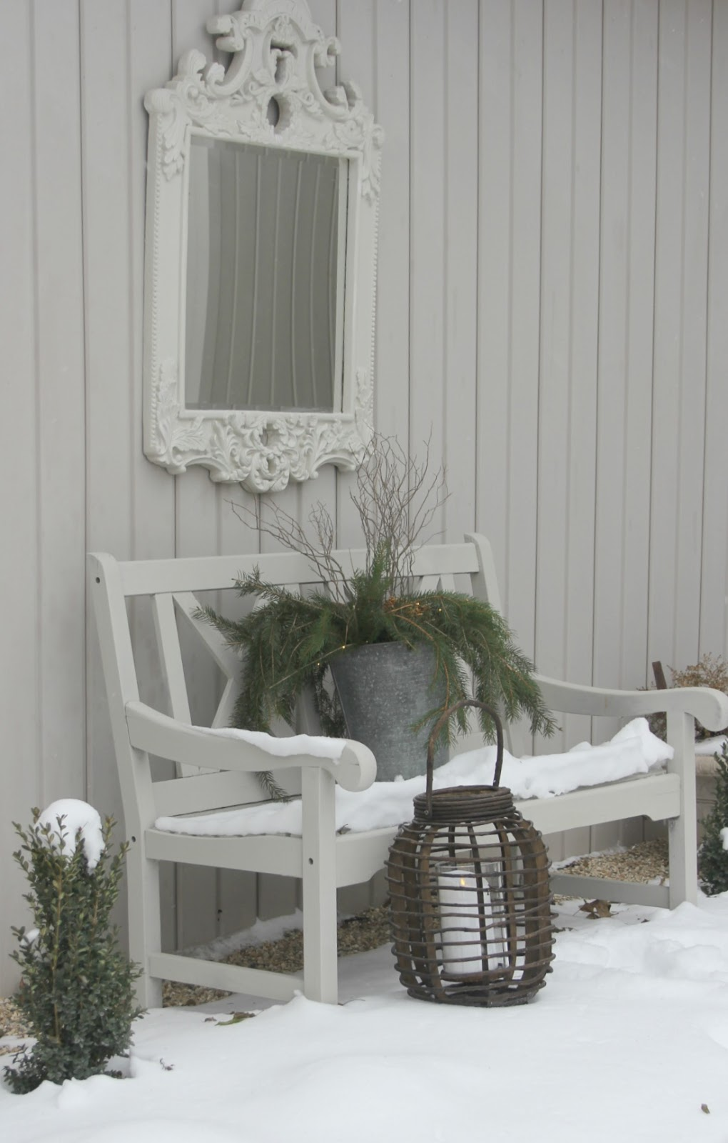 A Nordic French winter vignette with snow, bench, mirror, lantern, and rustic charm. Hello Lovely Studio.