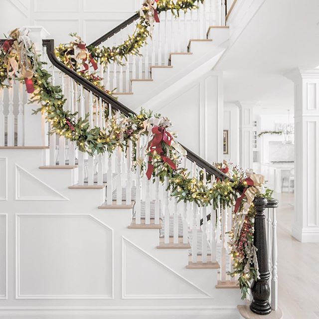Staircase with gorgeous greenery garland, white lights, and soft red ribbon. #christmasdecor #elegant #garland #staircase