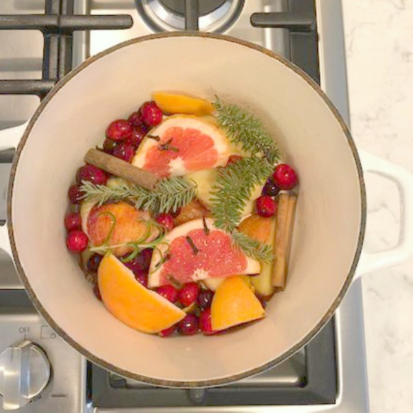 Bold color from fruit, evergreens, and cinnamon in a simmering stovetop potpourri - Hello Lovely Studio. #christmaskitchen #potpourri #holidaystyle #cozykitchen