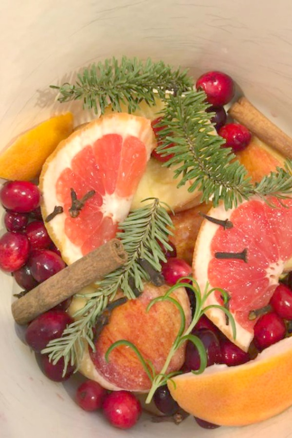 Christmas potpourri simmering on the stovetop. Grapefruit, rosemary, cranberries, cinnamon, and allspice! Hello Lovely Studio. #christmas #aroma #potpourri #simmering