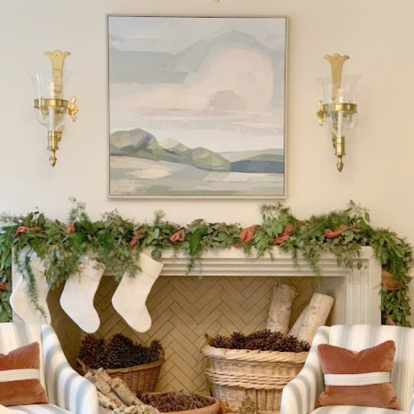Pale colors for a Christmas decorated living room with stone fireplace, white stockings, and simple fresh garland on mantel. #frenchcountry #whitechristmas #christmasdecor #holiday