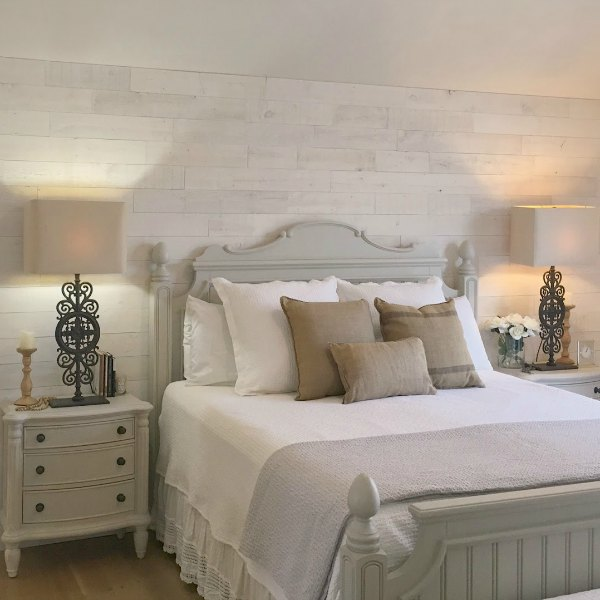 My serene white French country bedroom with Stikwood accent wall, cottage style wood furniture, Paris gate lamps (RH) and white oak flooring - Hello Lovely Studio.