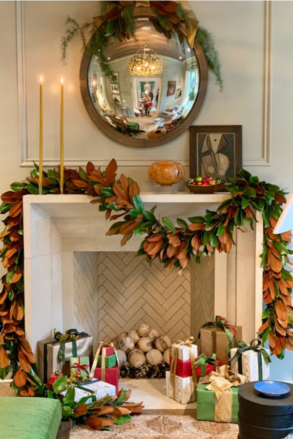 Elegant and sophisticated Christmas decor including a stone fireplace adorned with a magnificent fresh garland. Beautiful holiday decor inspiration from interior designers and bloggers. Come discover 28 Amazing Christmas Decorating Ideas! #christmasdecor #holidaydecorating