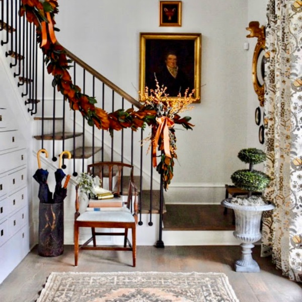 Beautiful staircase draped with neutral greenery for Christmas in a showhouse in Atlanta.