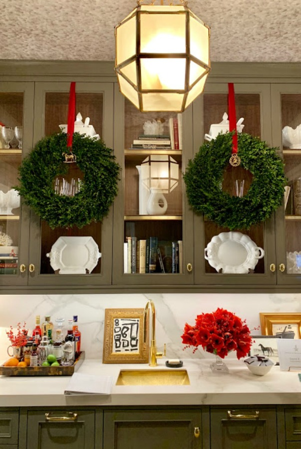Simple wreaths hung on from kitchen cabinets by solid red ribbon in a showhouse for Christmas decor. Beautiful holiday decor inspiration from interior designers and bloggers. Come discover 28 Amazing Christmas Decorating Ideas! #christmasdecor #holidaydecorating