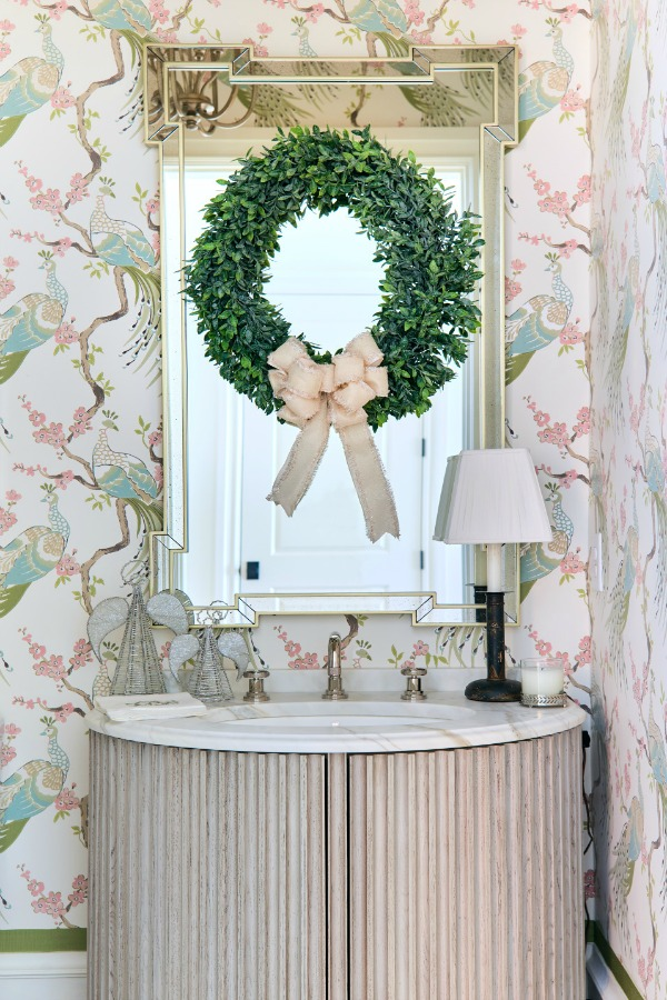 Beautiful fresh green Christmas wreath with ivory bow hung on a mirror in a powder room in an Atlanta showhouse. Beautiful holiday decor inspiration from interior designers and bloggers. Come discover 28 Amazing Christmas Decorating Ideas! #christmasdecor #holidaydecorating