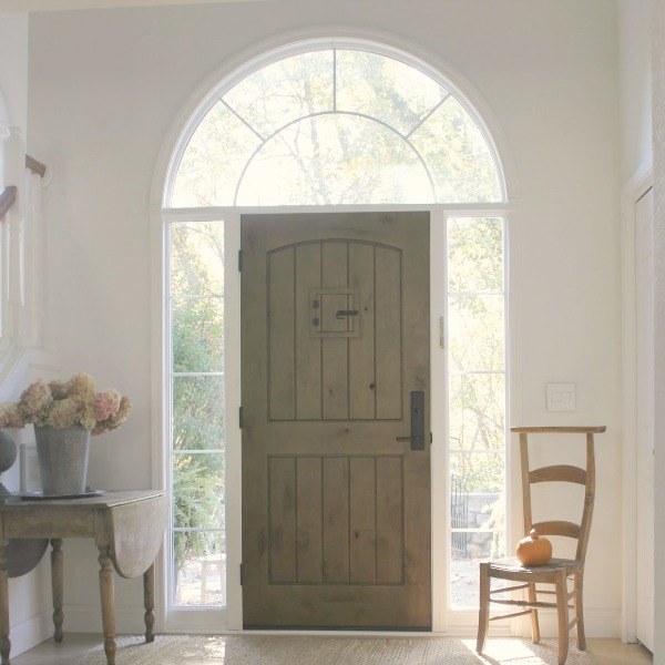 Knotty rustic alder wood planked front door with speakeasy in a lofty entry with antique dropleaf table, dried hydrangea, and French prayer chair  within a European Country cottage by Hello Lovely Studio.