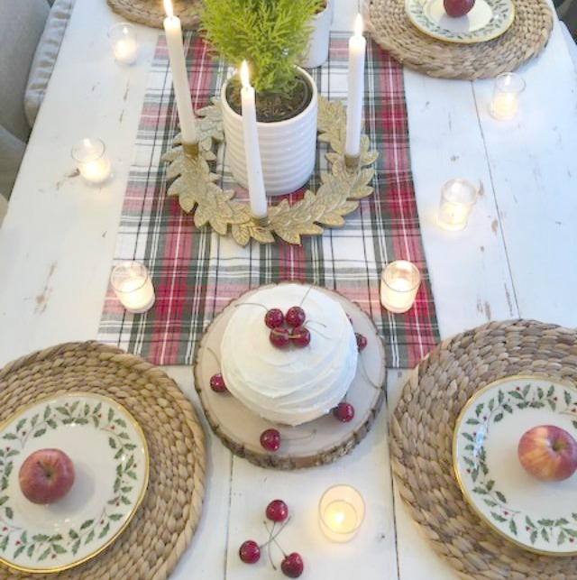 Farmhouse Christmas tablescape with red cherries, plaid, and holly Lenox plates. Hello Lovely Studio. Come find the mini cake recipe and sources for decor! #hellolovelystudio #tablescape #christmas #cherries #cake