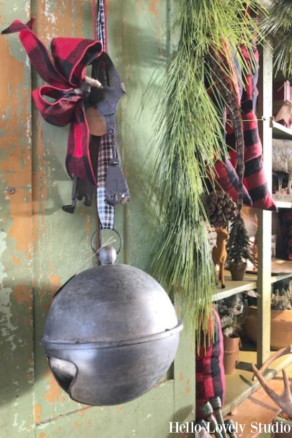 Oversized galvanized Christmas bell suspended from green vintage door at Trove Vintage. #holidaydecor #christmasdecorating #bell #vintagestyle