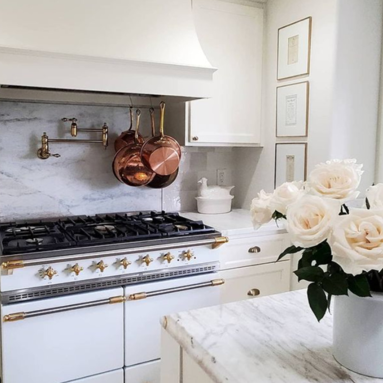 Glorious white French country kitchen with Lacanche range and copper pots - @thefrenchnestcointeriordesign. #frenchcountrykitchen #frenchkitchen #modernfrench