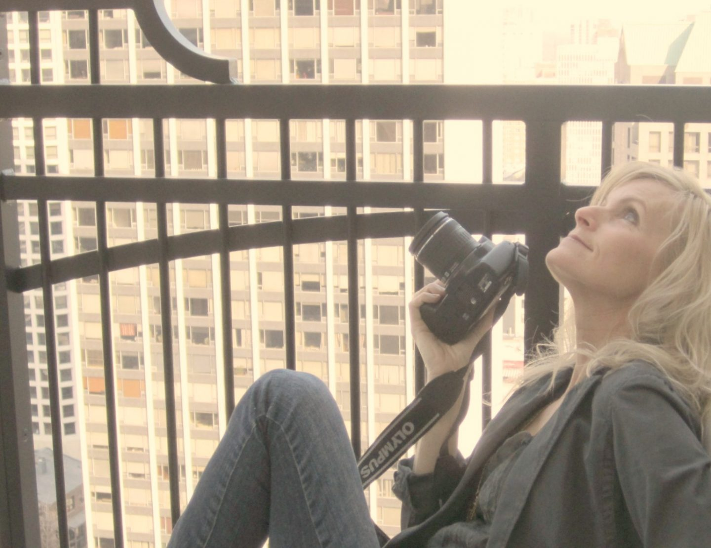 Michele of Hello Lovely Studio with camera on balcony of Waldorf Astoria Chicago. #hellolovelystudio