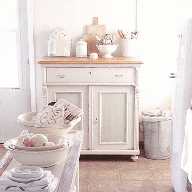 Nordic French farmhouse style in a white cottage kitchen by My Petite Maison with French ironstone, antique sideboard, and tone on tone decor.