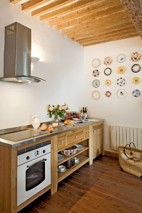 Decorative plates hung pleasingly on the wall of a French farmhouse kitchen near Provence. Haven In.