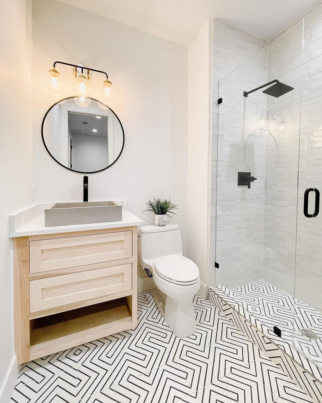 Stunning black and white cement tile flooring in bathroom (and zellige tile in shower) - @riadtile (design by @the.little.bird). #cementtile #tileflooring #bathroomtile