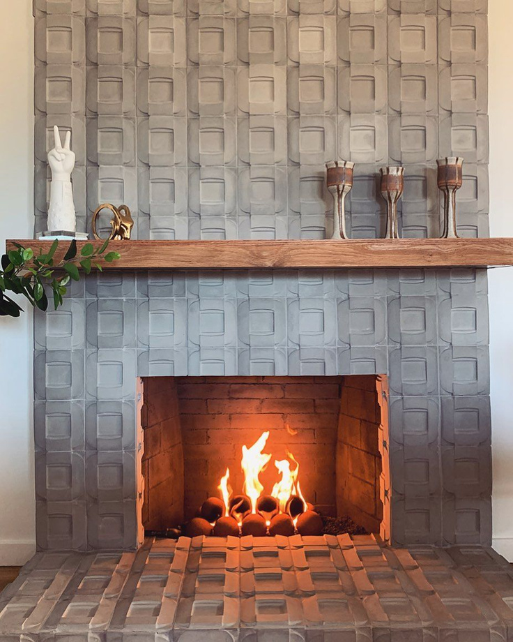 Edgy, dramatic, and organic, this cement tiled fireplace (@renoveau_hom) has geometric chic and rustic elegance. #cementtile #fireplace #interiordesign