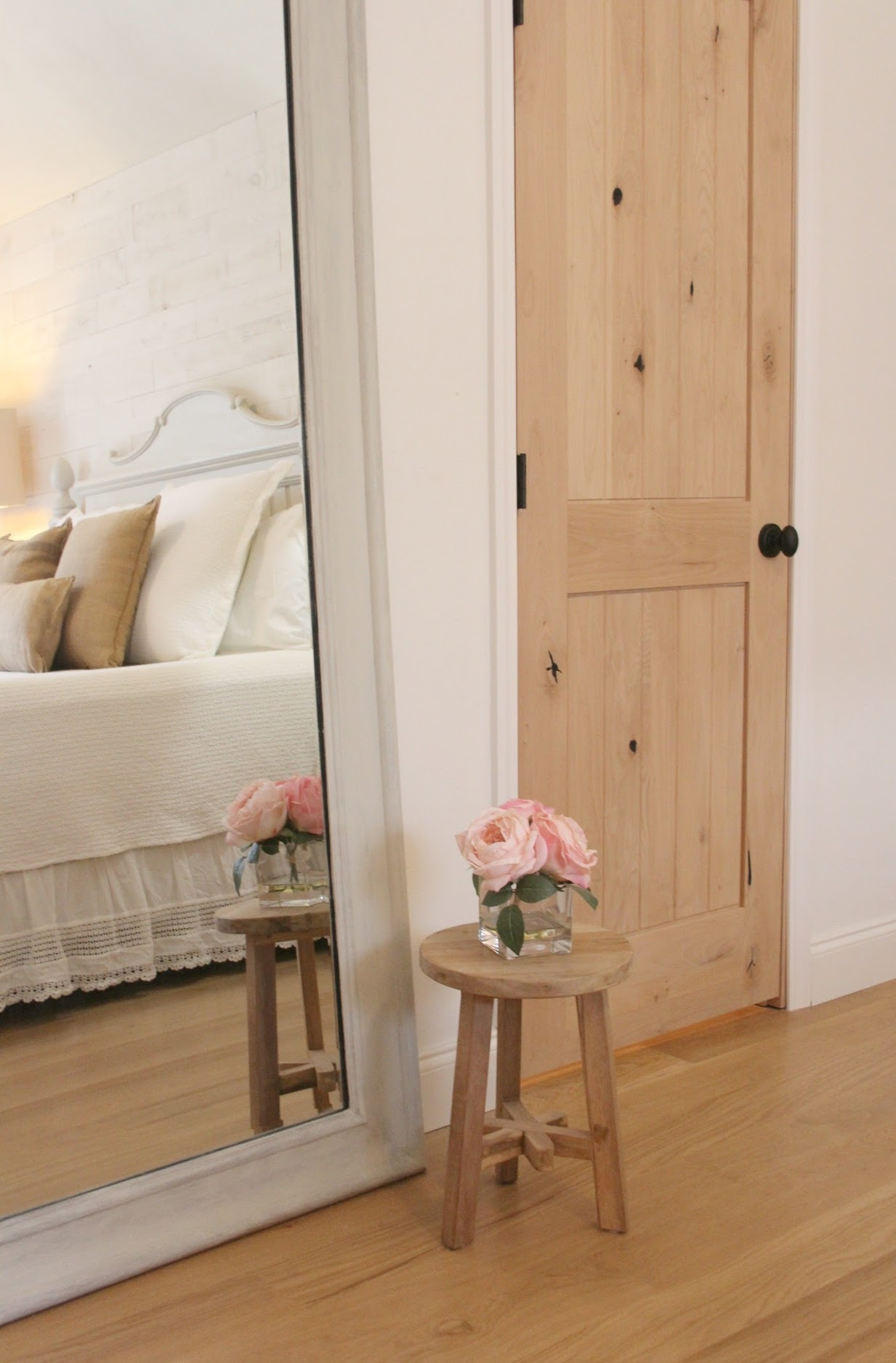 Knotty alder interior doors in our romantic cottage style bedroom and a rustic three leg teak stool. Hello Lovely Studio.