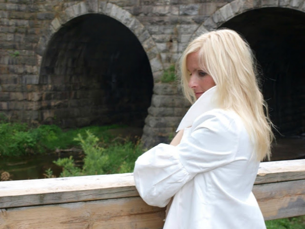 Michele of Hello Lovely Studio at historic stone bridge in white jacket with balloon sleeves. #hellolovelystudio