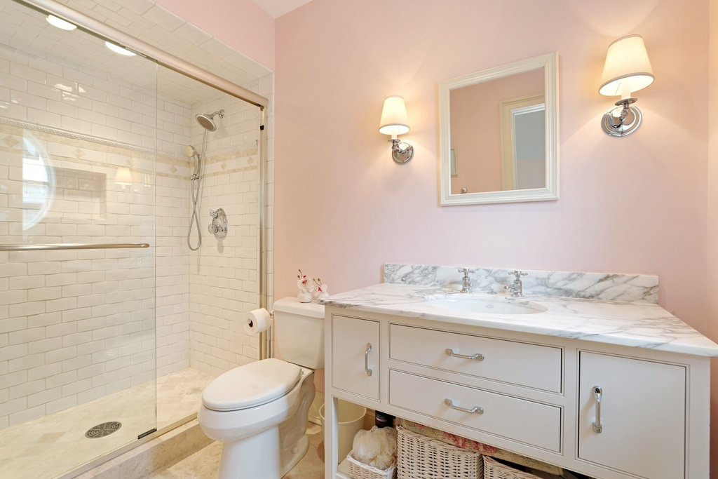 Beautiful pink walls in a classic and luxurious white bathroom in a Hinsdale manse. Come explore more Country French Decor Ideas from luxurious and grand homes.