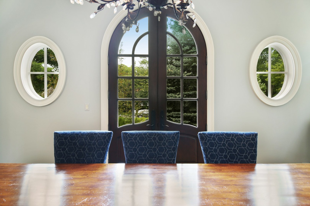 Oval windows and arched French doors in a dining room painted a soothing pale blue in a grand Hinsdale manse. Come explore more Country French Decor Ideas from luxurious and grand homes.