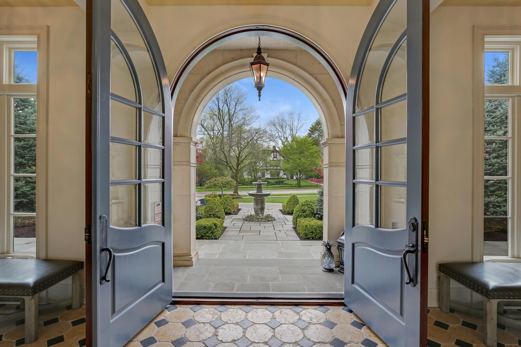 Grand double French arched doors at the entrance to a magnificent Hinsdale manse. Come explore more Country French Decor Ideas from luxurious and grand homes.