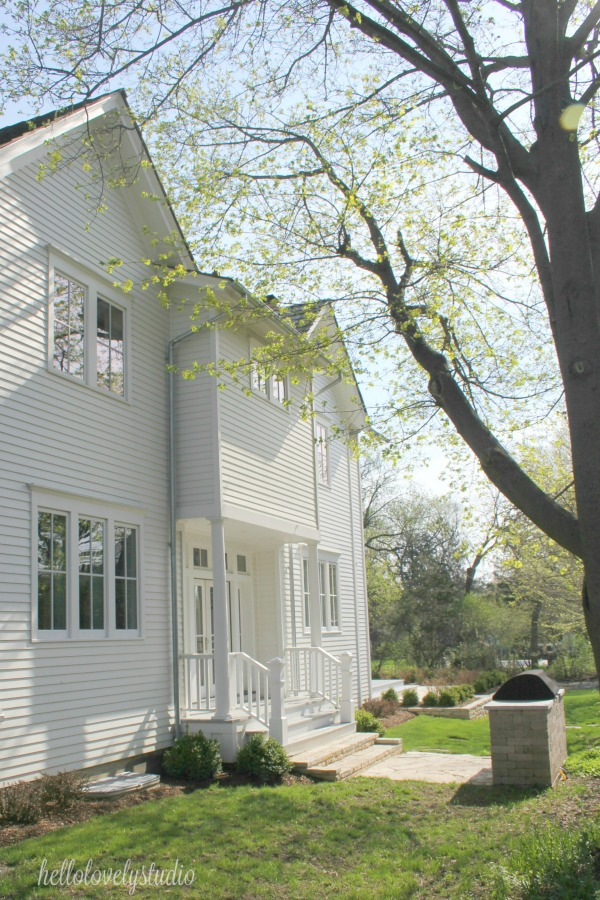 Modern farmhouse exterior - a beautiful white restored country house! Hello Lovely Studio.