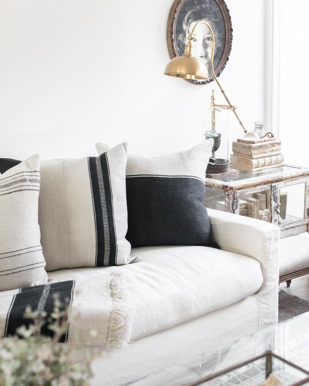 Detail of a linen Belgian style sofa with black accents on pillows in a modern rustic living room with design by @beautifulmesshome. #modernrustic #livingroom #belgianstyle