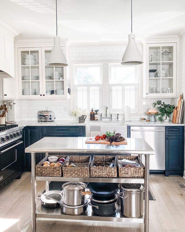 Stainless work table in industrial farmhouse kitchen with white pendants and two tone cabinets - Most Lovely Things. #stainlessworktable #industrialfarmhouse #farmhousekitchen