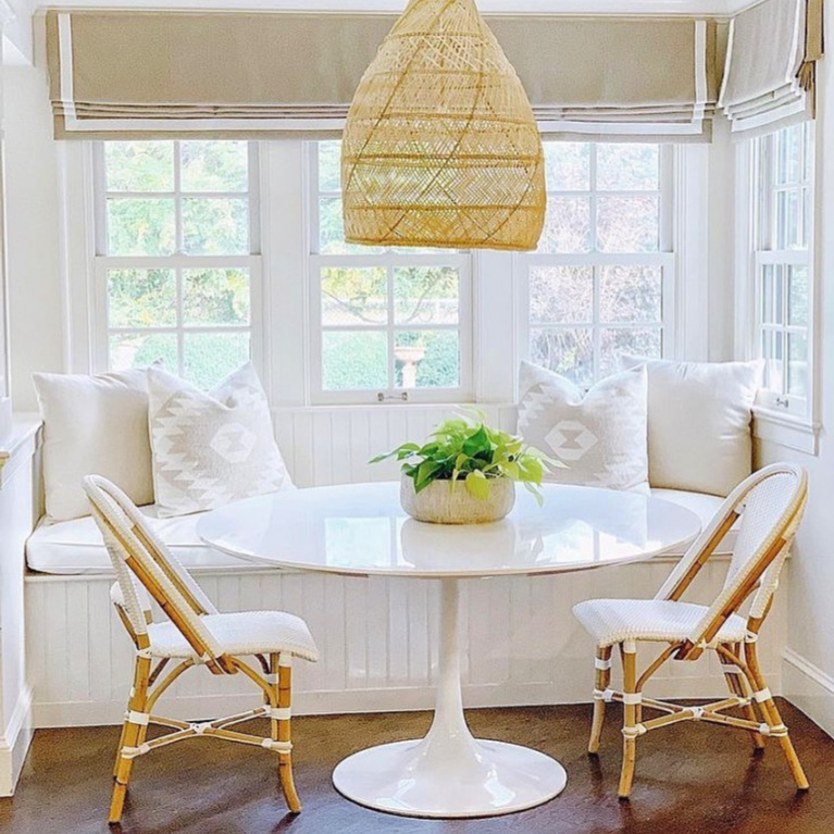 Lovely coastal white kitchen breakfast nook with Saarinen style table, banquette, wicker pendant, and Parisian bistro chairs from Serena & Lily. #breakfastnook #banquette #whitekitchen #windowseat #serenaandlily #saarinentable