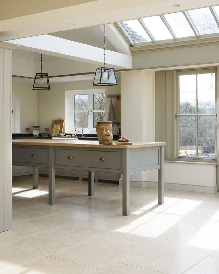 Exquisite and ethereal European country kitchen in an orangery with limestone tile floor and skylights featuring bespoke designs by deVOL.