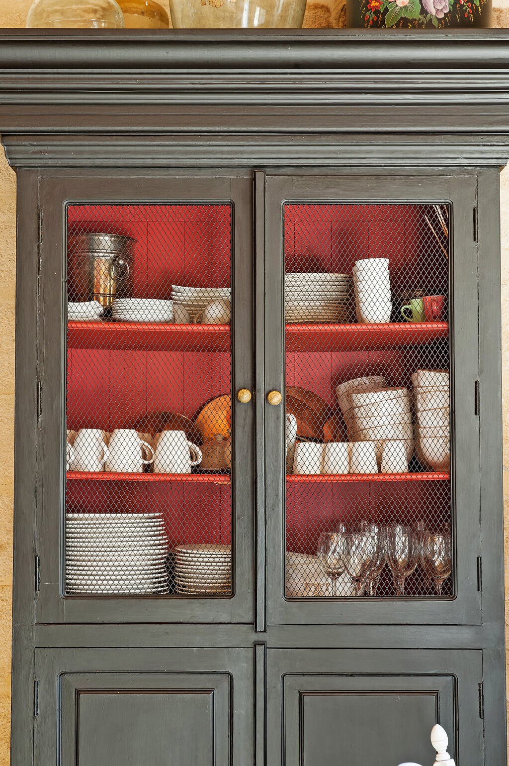 Charcoal grey French farmhouse cupboard with wire door inserts and red interior.
