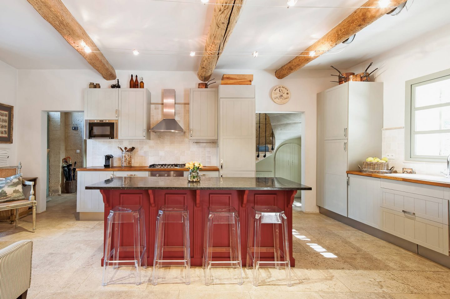 French farmhouse kitchen with modern cabinets and large center island with acrylic bar stools. Haven in.