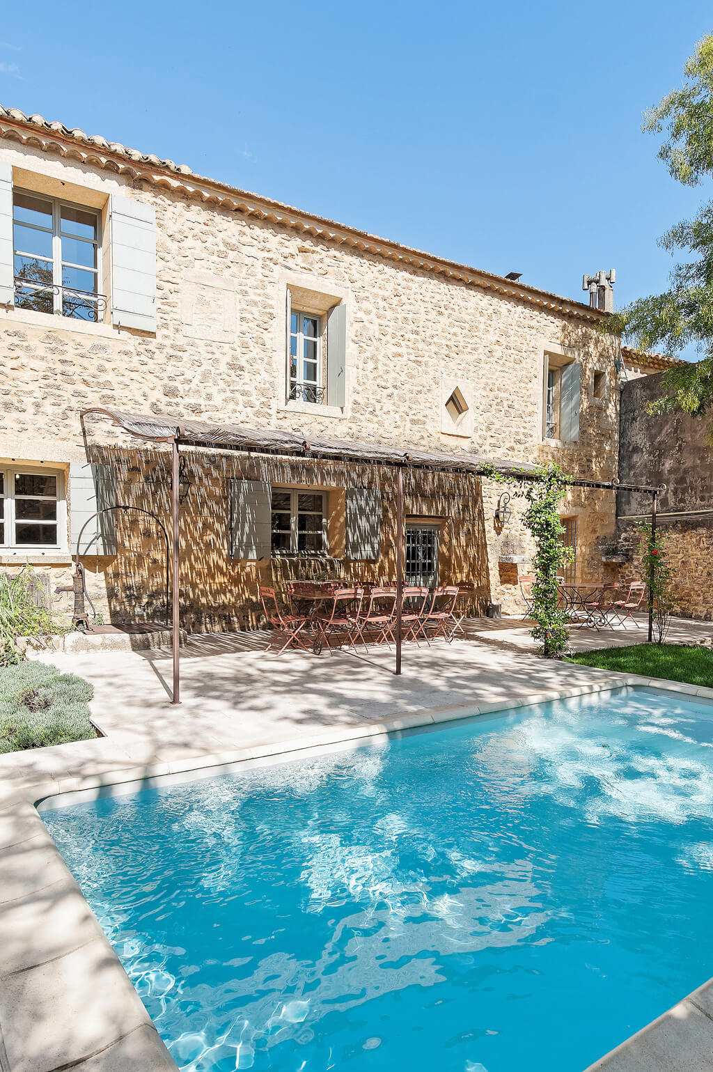 Provence farmhouse pool and outdoor dining in a charming setting.
