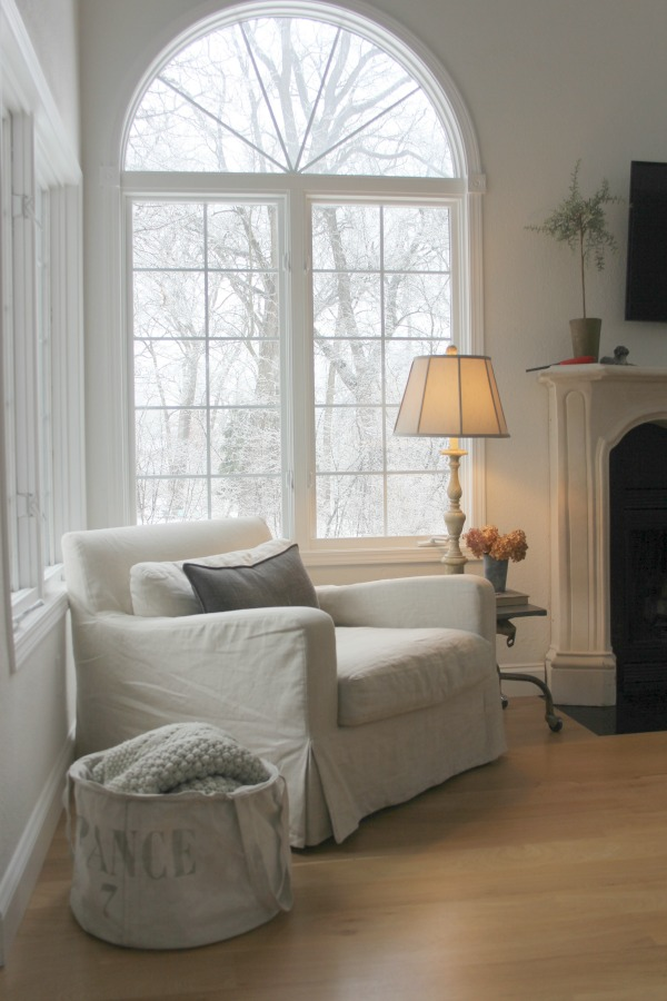 Belgian linen club chair in our living room with winter trees visible outside window. Hello Lovely Studio. Come visit 10 Smart Peaceful Ideas & Gifts to Give or Receive.