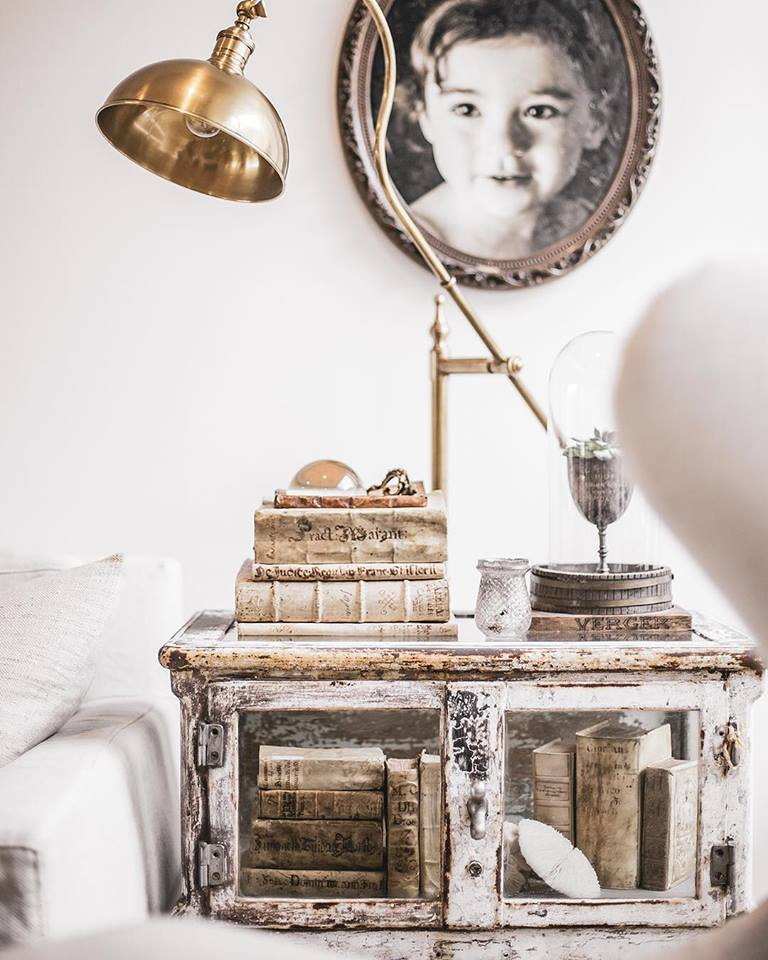 Beautiful weathered table and vellum books in a vignette by A Beautiful Mess Home.
