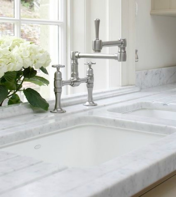 Detail of a beautiful undermount sink and marble countertop in a kitchen design by Artichoke.