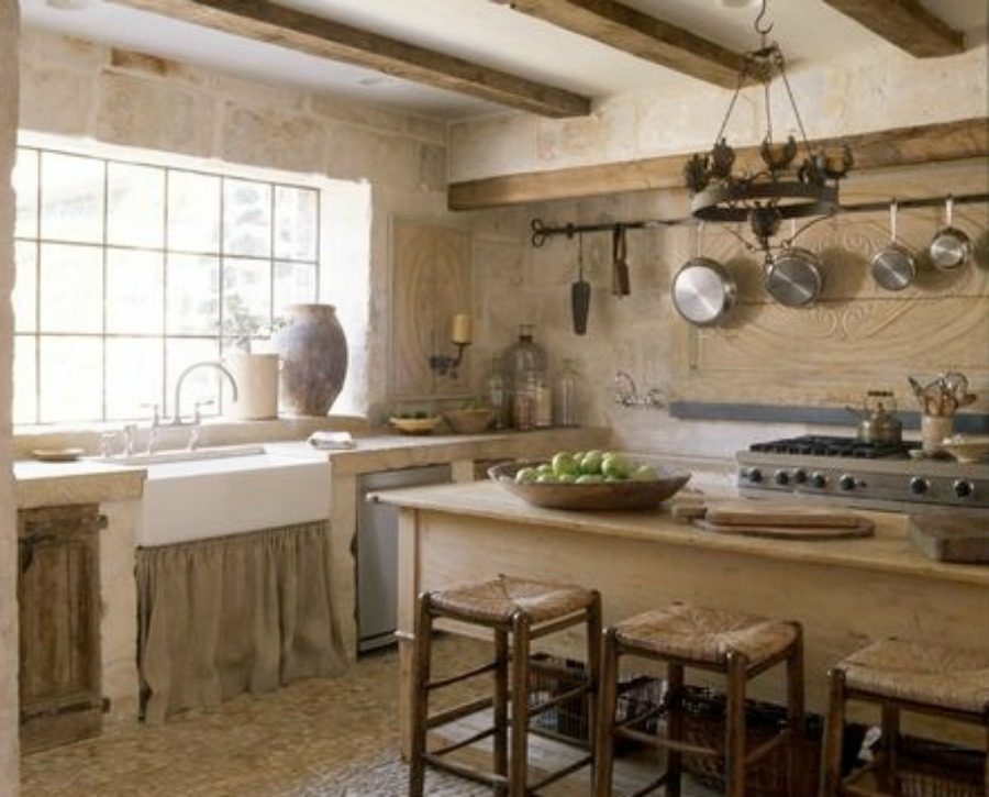 French farmhouse kitchen in Houston by Chateau Domingue with rustic stone, wood beams, and reclaimed cobblestone floor. #chateaudomingue #frenchkitchen #frenchfarmhouse