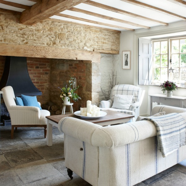 Cotswolds cottage living room with amazing stone fireplace and rustic wood beams.