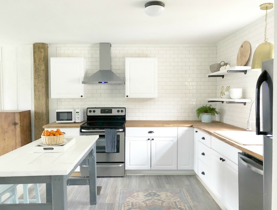 White cottage kitchen with subway tile, butcher block counters and stainless appliances.