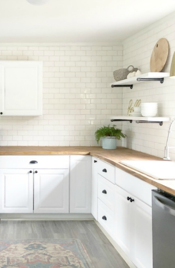 Charming white subway tile on backsplash in modern farmhouse kitchen with butcher block counters.