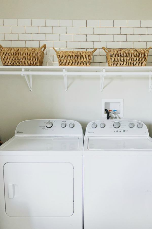 White subway tile above washer and dryer.