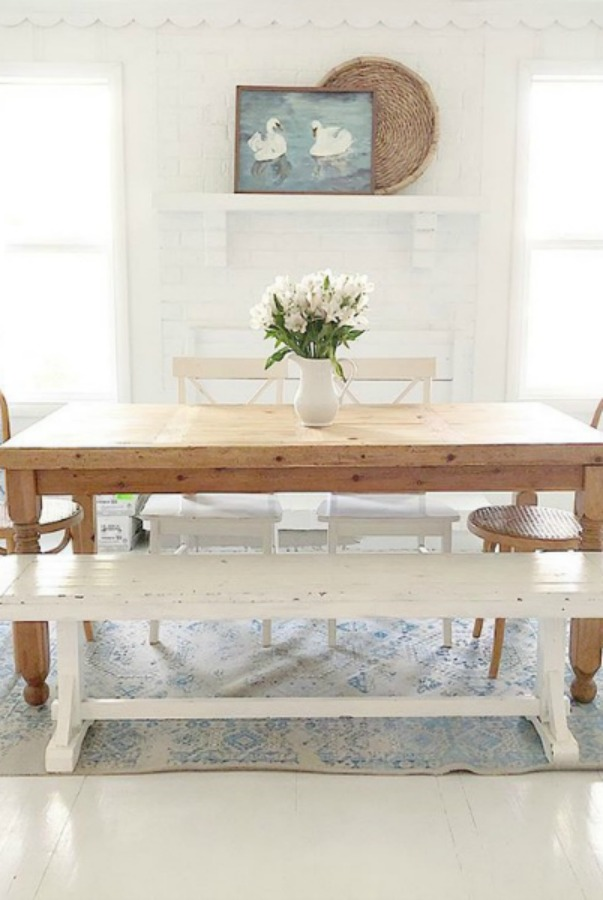 Rustic modern country dining room with wood table and white chairs.