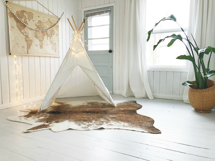 White teepee, fairy lights, and cowhide rug in white painted paneled modern farmhouse room.