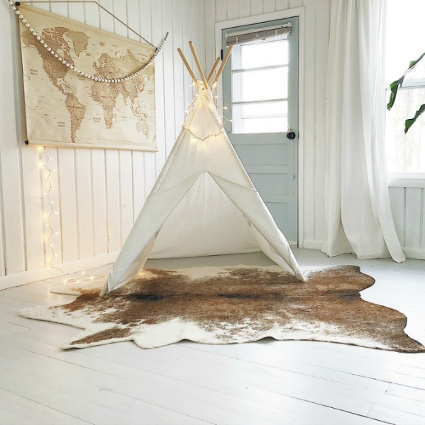 White teepee and cowhide rug in modern farmhouse kids space with paneled walls.