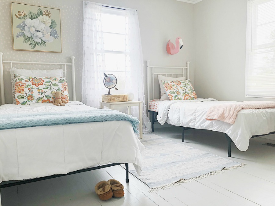 Charming kids room with cottage style white beds and soft color palette.
