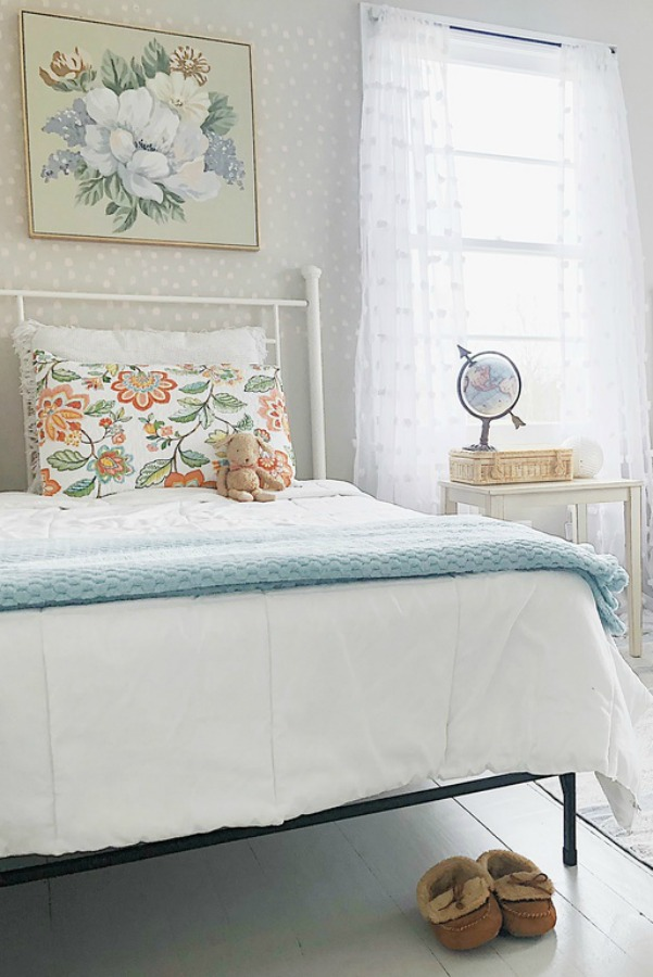 Lovely vintage style shabby chic cottage bedroom with white metal bed.
