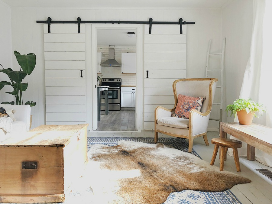 White barn doors in modern farmhouse space with wing chair.