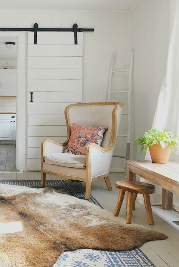 French style wing chair and cowhide rug in modern farmhouse.