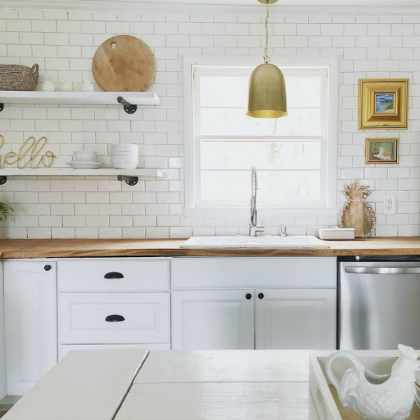 White modern farmhouse kitchen with subway tile statement wall and brass dome pendant light over sink.