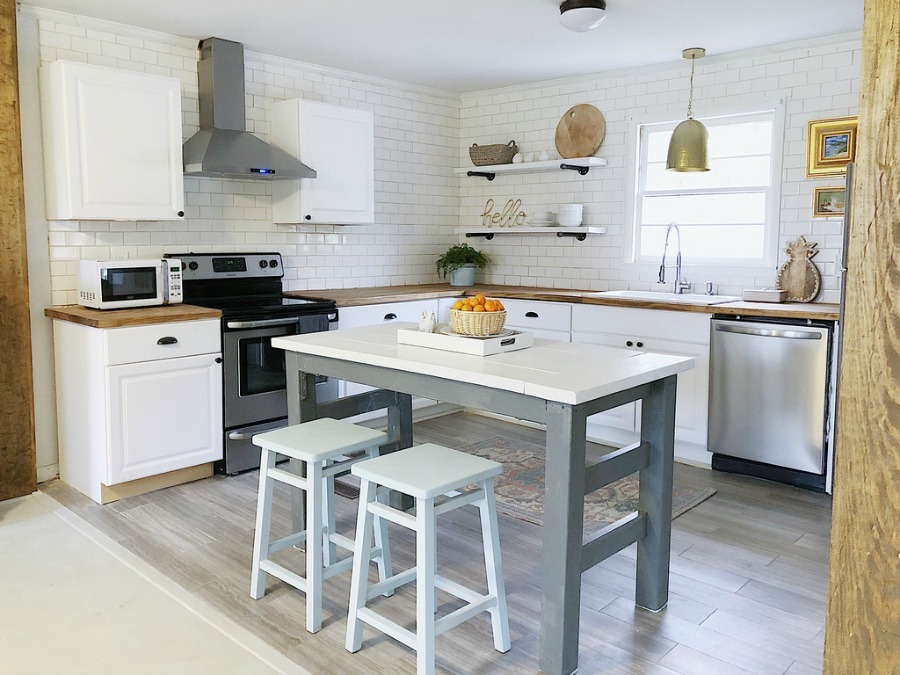 Charming modern farmhouse white kitchen with work table and butcher block counters.