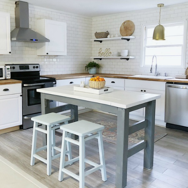 Simple white modern farmhouse kitchen with subway tile and work island in a Tennessee kitchen.